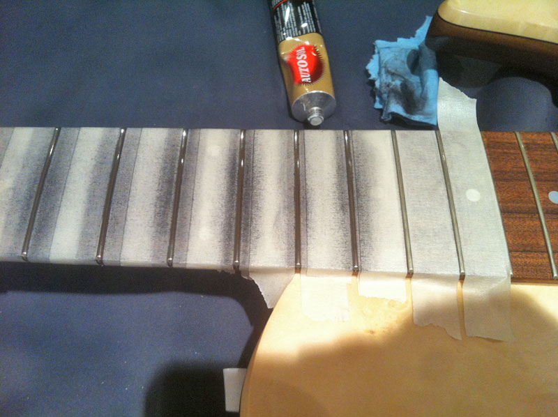 rubbing the fret with metal polish